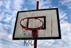 Canasta de baloncesto con redes metálicas y cielo con nubes